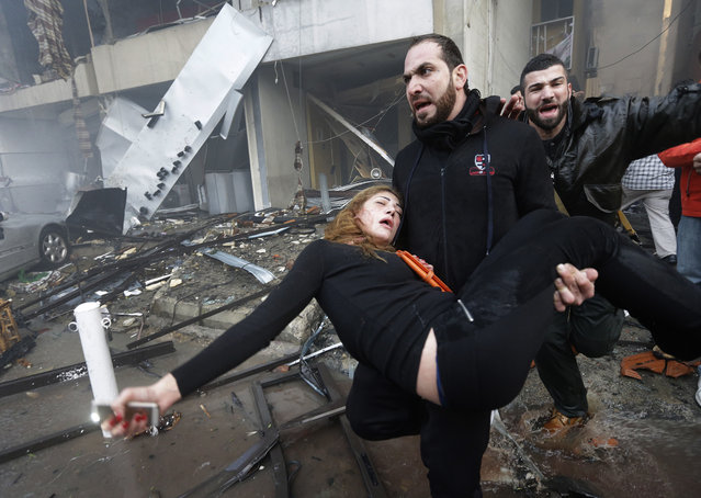 A Lebanese man carries an injured woman away from the site of a car bomb explosion in a Shiite area and stronghold of the Lebanese militant group Hezbollah at the southern suburb of Beirut, Thursday Jan. 2, 2014