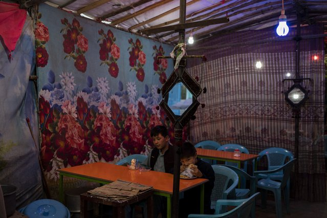 Two boys eat at a local restaurant in Kabul, Afghanistan, Friday, September 10, 2021. (Photo by Bernat Armangue/AP Photo)