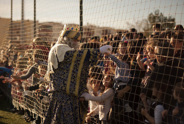 A men dressed as King Melchior meets children upon his arrival with men dressed as Kings Balthazar and Caspar, otherwise known as the three wise men or Kings, in Fuengirola, southern Spain, during an Epiphany street parade on January 5, 2014. The parades are held each year on the eve of the Feast of the Epiphany, which celebrates the gospel story of the coming of three wise men to bring gifts to the Christ child. (Photo by Jorge Guerrero/AFP Photo)