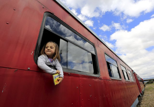 "A girl looks out from the window of a ""La Sabana"" tourist train in La Caro March 1, 2015. (Photo by Jose Miguel Gomez/Reuters)"