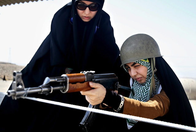 In this Thursday, August 22, 2013 photo, a female member of the Basij paramilitary militia aims a rifle as a trainer looks over her shoulder in Tehran, Iran. (Photo by Ebrahim Noroozi/AP Photo)