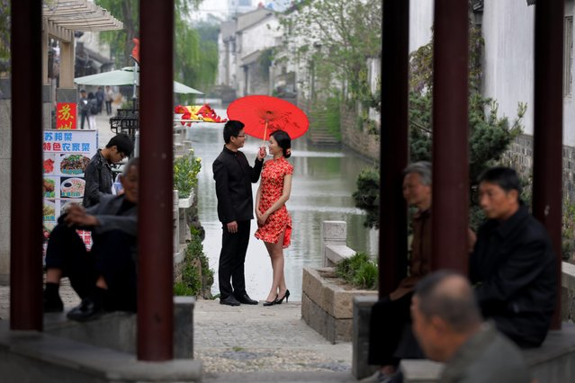 Residents take rest at a pavilion as a bride and groom, dressed a traditional costume, pose for wedding photos near Pingjiang steet in Suzhou in east China's Jiangsu province, Thursday, April 16, 2015. Pingjiang street was built along a canal and existed as early as the Song Dynasty, and is one of the famous tourist attractions in the country. (Photo by Andy Wong/AP Photo)