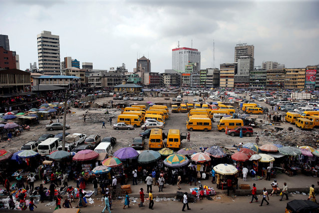 People walk past roadside stalls with umbrellas in the central business district, near Marina in Lagos, Nigeria December 13, 2016. (Photo by Akintunde Akinleye/Reuters)