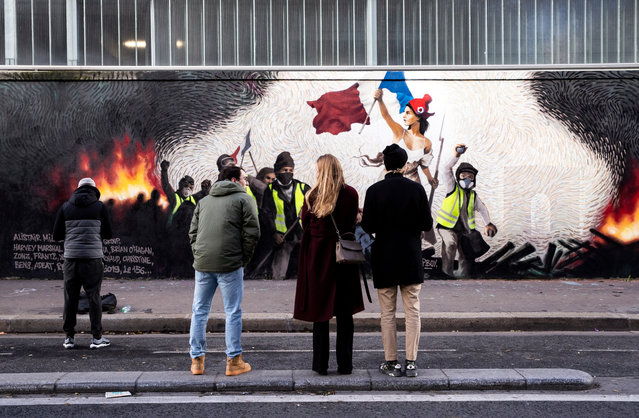 """People look for clues to get a reward hidden in a mural reproducing a """"Yellow Vests"""" version of Eugene Delacroix """"Liberty Leading the People"""" by French crypto-artist Pascal Boyart in Paris, France, 08 January 2019. The artist hid clues leading to a digital wallet containing 0,26 Bitcoin around 900€. (Photo by Etienne Laurent/EPA/EFE)"""