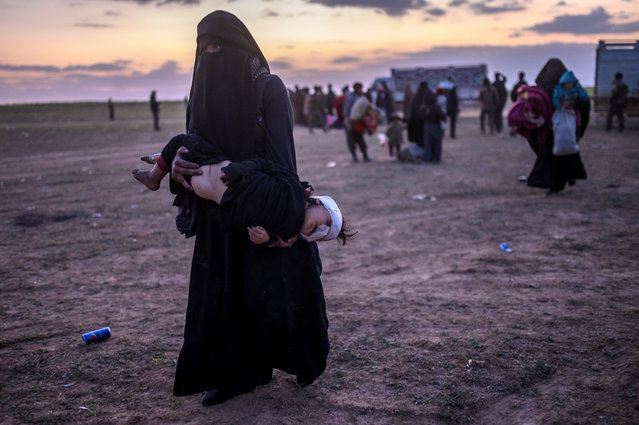 """A fully veiled woman carries her injured child as she walks to members of the Kurdish-led Syrian Democratic Forces (SDF) just after leaving the Islamic State group's last holdout of Baghouz, in the eastern Syrian Deir Ezzor province on March 4, 2019. The capture of Baghouz would mark the end of IS territorial control in the region and deal a death blow to the """"caliphate"""", which once covered huge swathes of Syria and Iraq. (Photo by Bulent Kilic/AFP Photo)"""