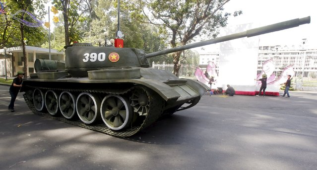 A man pushes a mock military Tank 390, which was operated by North Vietnamese forces and  first crashed through the gate of the former presidential palace, past the palace after a rehearsal for a military parade as part of the 40th anniversary of the fall of Saigon, in southern Ho Chi Minh City (formerly Saigon City), Vietnam, April 26, 2015. (Photo by Reuters/Kham)