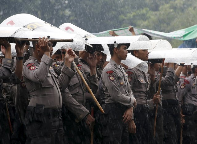 Police use their riot shields to shelter from the rain during a protest by taxi drivers outside the presidential palace Jakarta, Indonesia March 14, 2016. (Photo by Darren Whiteside/Reuters)