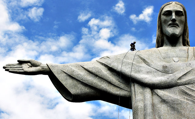 A worker hauls in a rope while perched on the shoulder of the Christ the Redeemer statue during a media tour following a ceremony blessing the workers by the Archbishop of Rio de Janeiro, Dom Orani Tempesta, on February 14, 2014 in Rio de Janeiro, Brazil. (Photo by Mario Tama/Getty Images)