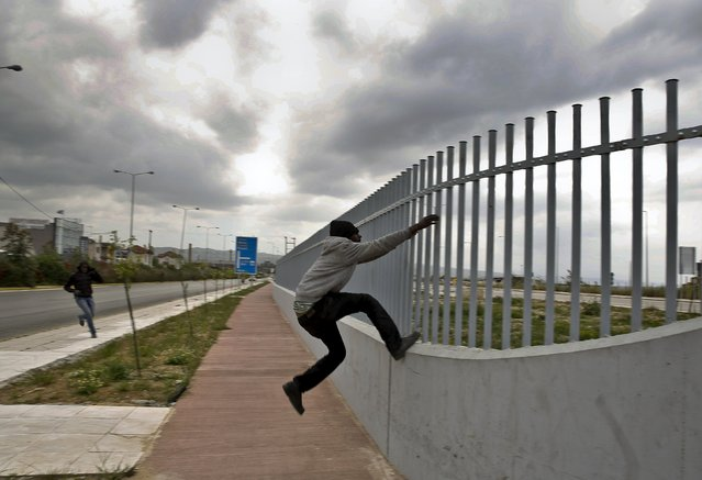 An African immigrant tries to jump a fence into a ferry terminal in the western Greek town of Patras April 28, 2015. (Photo by Yannis Behrakis/Reuters)