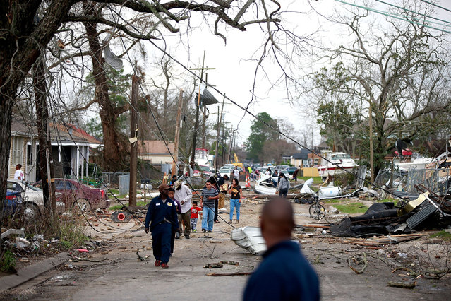 Residnets walk down a street along Chef Menture Ave after a tornado touched down in the eastern part of the city on February 7, 2017 in New Orleans, Louisiana. Accoriding to the weather service 25 people were injured in the aftermath of the tornado. (Photo by Sean Gardner/Getty Images)