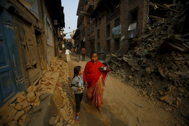 A woman and a child returning from a temple, walk past damaged and collapsed houses following April 25 earthquake at Bhaktapur May 7, 2015. (Photo by Navesh Chitrakar/Reuters)