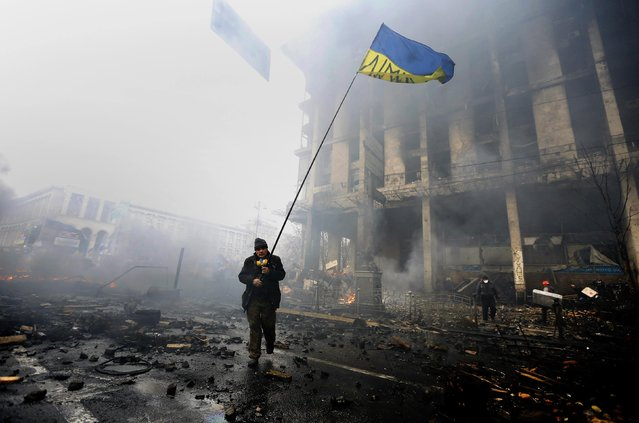An anti-government protester holds a Ukranian flag as he advances through burning barricades in Kiev's Independence Square February 20, 2014. (Photo by Yannis Behrakis/Reuters)