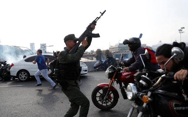 "Soldiers and people react to the sound of gunfire near the Generalisimo Francisco de Miranda Airbase ""La Carlota"", in Caracas, Venezuela April 30, 2019. (Photo by Carlos Garcia Rawlin/Reuters)"