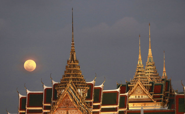 In this January 31, 2018, file photo, a full moon rises behind the Grand Palace in Bangkok, Thailand. The official coronation of Thailand's King Maha Vajiralongkorn, who is also known as Rama X, involves months of rituals that will culminate in three days of elaborate pageantry, including a parade and an appearance by the king on a balcony of the Grand Palace. The final event will be a royal barge procession in October, 2019. (Photo by Sakchai Lalit/AP Photo/File)