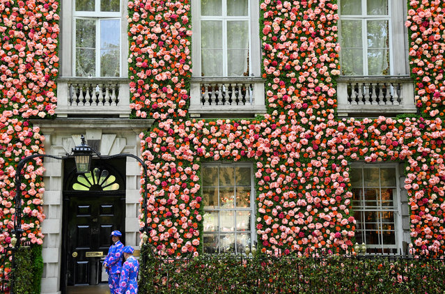 Doormen dressed in floral patterned suits stand on duty outside of a private club with it's front covered in flowers in London, Britain, May 15, 2019. (Photo by Toby Melville/Reuters)