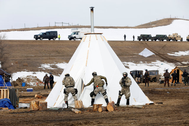 Law enforcement officers cut open a shelter in the main opposition camp against the Dakota Access oil pipeline near Cannon Ball, North Dakota, U.S., February 23, 2017. (Photo by Terray Sylvester/Reuters)