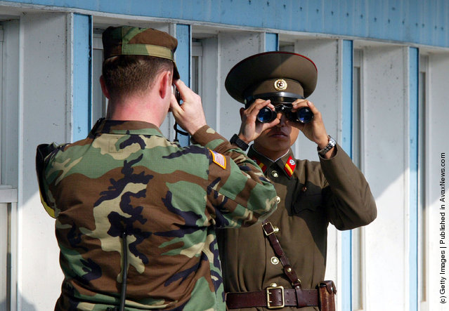 A U.S. soldier (L) takes picture of a North Korean soldier as he stands guard