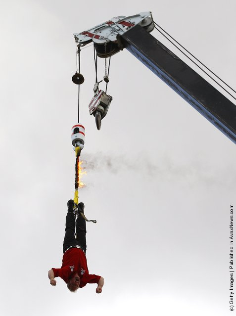 Canadian escape artist Dean Gunnarson attempts to work his way out of a straight jacket while hanging from a crane by a rope which is on fire during a Royal Melbourne Show