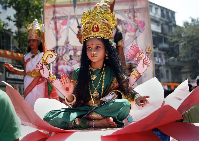 "A young Indian girl dressed as Hindu goddess Laxmi participates in a procession to mark ""Gudi Padwa"", or Maharashtrian New Year, in Mumbai, in the Indian state of Maharashtra, Friday, April 8, 2016. (Photo by Rajanish Kakade/AP Photo)"