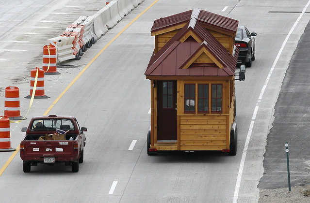 A Tumbleweed brand Cypress 24 model Tiny House is towed down the highway near Boulder, Colorado August 4, 2014. The Tiny House Movement started some years ago with people around the world building really small living spaces and loving their new simplified lives. (Photo by Rick Wilking/Reuters)