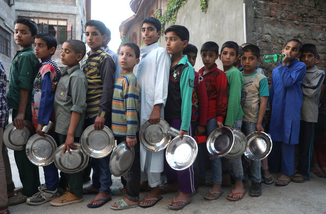 Kashmiri Muslim orphan children wait in a queue to receive food to break the fast at Rahat Manzil (Yateem Khana), an orphanage in Srinagar, the summer capital of Indian Kashmir, 21 May 2019. Muslims around the world celebrate the holy month of Ramadan by praying during the night time and abstaining from eating, drinking, and sexual acts during the period between sunrise and sunset. Ramadan is the ninth month in the Islamic calendar and it is believed that the revelation of the first verse in Koran was during its last 10 nights. (Photo by Farooq Khan/EPA/EFE)