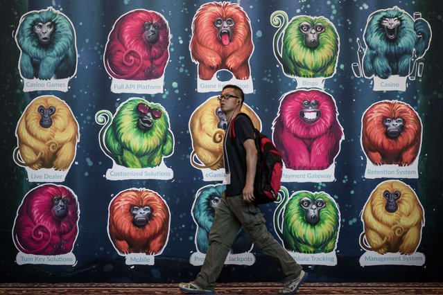 A man walks past a billboard at the Global Gaming Expo Asia in the world's biggest gambling hub of Macau on May 20, 2015. The three-day fair of gambling innovations, the largest gaming event in Asia, showcases the industry's latest products, services and technologies at the glitzy Venetian Macau hotel. (Photo by Philippe Lopez/AFP Photo)