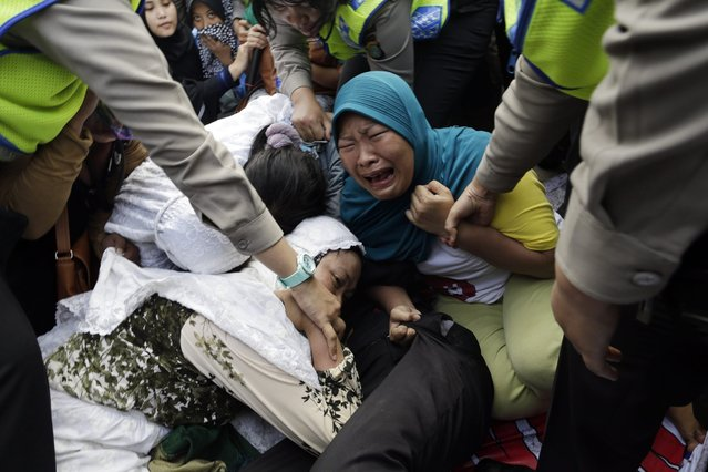 Indonesian public order agency security officers pull up protesting residents from the road during the demolition of illegal houses at a slum area in Jakarta, Indonesia, 11 April 2016. The Jakarta administration deployed at least 4,000 personnel including police, military and members of the public order agency to begin the demolition process of the Luar Batang neighborhood in North Jakarta. According to media reports, more than 500 makeshift houses and permanent residences were demolished as the government plans to increase public spaces and tourist attractions in the area. (Photo by Mast Irham/EPA)