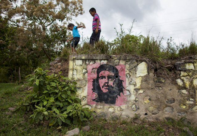 "Children play near an image of revolutionary hero Ernesto ""Che"" Guevara outside their house in Asturia town in northern Nicaragua May 23, 2015. (Photo by Oswaldo Rivas/Reuters)"