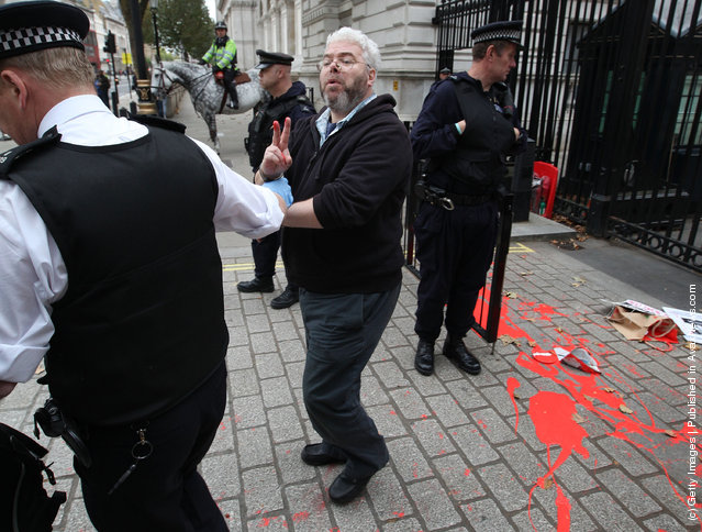 An anti-war protestor is detained by a policeman at the gates of Downing Street