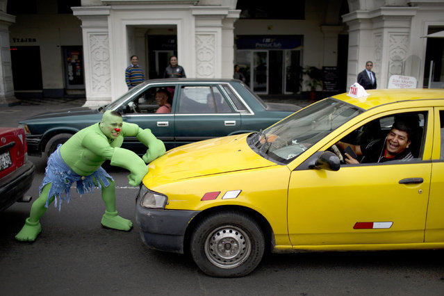 A clown acting as Hulk performs, pretending to stop a taxi during a march commemorating the Peruvian clown day in Lima Peru, Monday, May 25, 2015. (Photo by Rodrigo Abd/AP Photo)