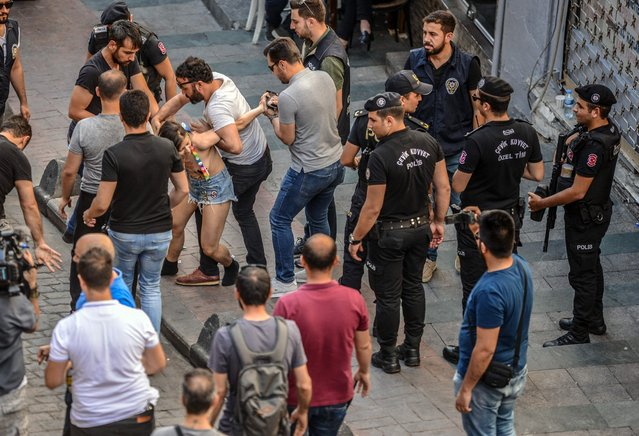 Turkish police detain a member of the LGBTQ+ community after taking part in the Gay Pride parade in Istanbul, on June 30, 2019. Turkish police on June 30 fired tear gas at gay rights groups and activists who defied authorities to march for the Istanbul pride parade, banned for the fifth year in a row. Thousands of people rallied close to the popular Istiklal Avenue and Taksim Square where organisers originally planned to hold the parade, an AFP correspondent said. (Photo by Tuba Kara/AFP Photo)