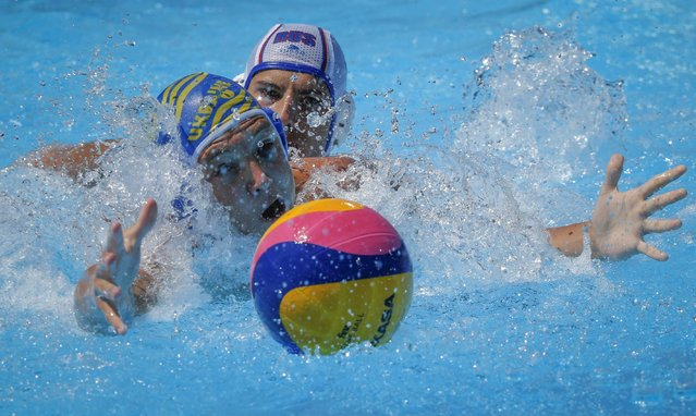 Denys Gusakov of Ukraine, left, fights for the ball with Daniil Pronin of Russia during the water polo competition at the 2015 European Games in Baku, Azerbaijan, Saturday, June 13, 2015. (AP Photo/Dmitry Lovetsky)