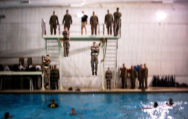 "Newly commissioned second lieutenants assigned to Bravo Company, The Basic School, perform an ""abandon ship"" technique during Marine Corps Water Survival Training Program qualification at Ramer Hall Swim Tank, Marine Corps Base Quantico, Va., January 17, 2013. About 300 second lieutenants trained to drown-proof in open water, survive in freezing water and move with a combat load in both shallow and deep water along with other water-survival techniques. (Photo by Marines Sgt. Tyler L. Main/Defense Media Activity)"