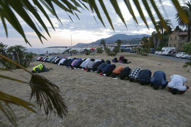 Migrants kneel in prayer at the Franco-Italian border in Ventimiglia, Italy, Wednesday, June 17, 2015. European Union nations failed to bridge differences Tuesday over an emergency plan to share the burden of the thousands of refugees crossing the Mediterranean Sea, while on the French-Italian border, police in riot gear forcibly removed dozens of migrants. (AP Photo/Lionel Cironneau)