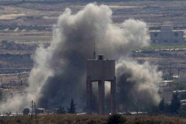 Smoke and explosions from fighting between forces loyal to Syrian President Bashar Assad and rebels in the Quneitra area of Syria are seen from the Israeli-occupied Golan Heights, Wednesday, June 17, 2015. Syrian rebels launched a wide-ranging offensive against Syrian government positions near the Golan Heights on Wednesday, after tit-for-tat shelling in and around Damascus left at least 33 people dead, activists said. Insurgents have been on the offensive in southern Syria for the past three months, capturing military bases, villages and a border crossing point with Jordan. (AP Photo/Ariel Schalit)