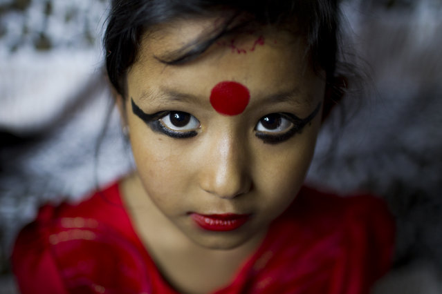 "Nepal newly appointed ""Living goddess"" Unikia Bajracharya known as Kumari, poses for the photographer at her home before she attends traditional rituals with priests in Patan, Nepal, 09 April 2014. Seven-year-old Unika was chosen to become the new Kumari of Patan after the previous Kumari, Samita Bajrachary, aged 12, reached the puberty, which means that she is considered ritually unclean. (Photo by Narendra Shrestha/EPA)"