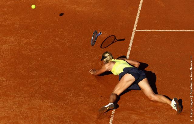 Maria Sharapova of Russia falls during her semi final match against Caroline Wozniacki of Denmark
