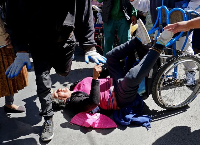 A demonstrator with physical disability falls from a wheelchair during a protest to demand that the government increase the monthly disability subsidy in La Paz, Bolivia April 27, 2016. (Photo by David Mercado/Reuters)