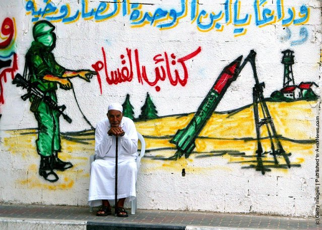 An elderly Palestinian man sits in front of a wall with a mural showing a masked militant from Ezz El-Deen Al-Qassam Martyrs' Brigade, the military wing of the Islamic resistance movement Hamas, as he fires a homemade Qassam rocket towards Israeli settlements, in Jabaliya refugee camp northern Gaza Strip August 28, 2003
