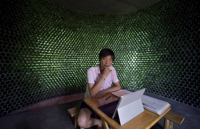 College graduate Li Rongjun poses for a photograph in a building made of 8,500 beer bottles, near his home in Lanya village of Chongqing municipality, China, June 26, 2015. (Photo by Reuters/Stringer)