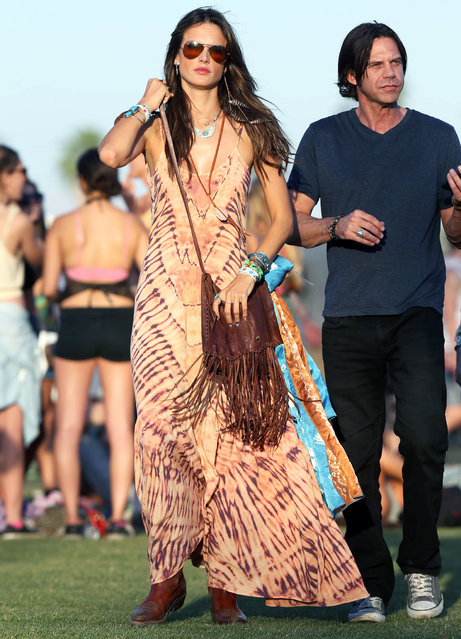"""Alessandra Ambrosio dances in the field at Coachella festival.  Alessandra was seen dancing while watching a performance by """"The naked and Famous"""" on the main stage. The Brazilian model wore a maxi dress,aviator sunglasses and had silver painted designs on her arms and back. (Photo by Splash News)"""
