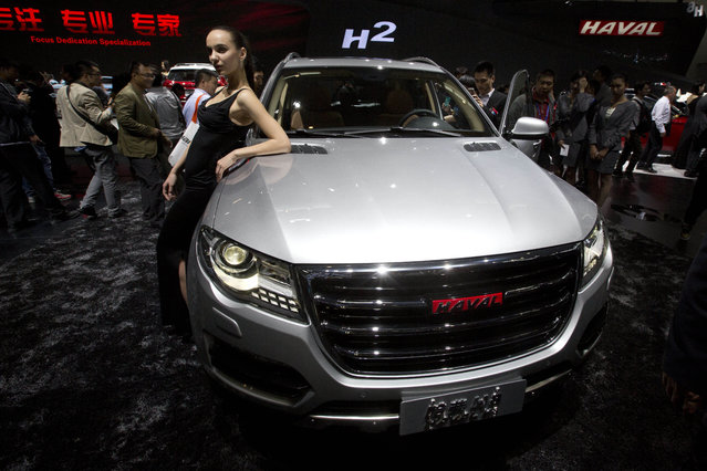A model poses near Chinese SUV maker Great Wall Motors' Haval 8 displayed at the China Auto show held in Beijing, China, Sunday, April 20, 2014. Automakers are looking to China's biggest auto show this year to help boost sales in this huge but cooling market. (Photo by Ng Han Guan/AP Photo)