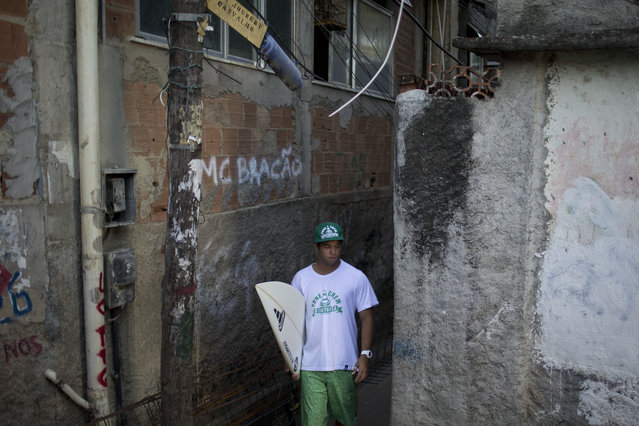 """In this June 10, 2015 photo, Magno Neves walks in an alley in the Cantagalo slum on his way to the nearby Arpoador beach in Rio de Janeiro, Brazil. """"My dream until today is to be a pro surfer"""", said Neves, who works as a dog-walker to make ends meet. (Photo by Felipe Dana/AP Photo)"""