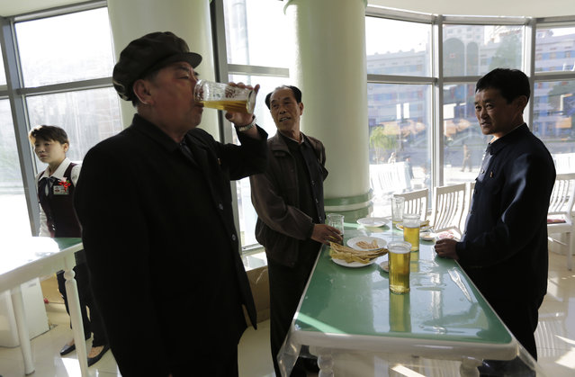 In this Saturday, May 7, 2016, photo, Pak Sun Won, 66, left, a retired physician drinks a glass of draft beer at the Taedonggang Beer shop with his friends in Pyongyang, North Korea. (Photo by Wong Maye-E/AP Photo)