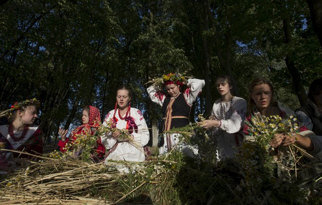 """Belarussian women make wreaths as they take part in the festival of national traditions """"Piatrovski"""" in the village of Shipilovichi, south of Minsk, July 12, 2015. (Photo by Vasily Fedosenko/Reuters)"""