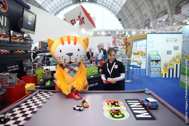 sales representative and toy character play with radio-controlled cars on display at  the 2012 London Toy Fair