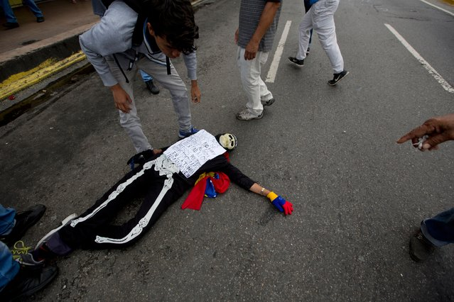 An anti-government demonstrator in costume lies on the ground, affected by tear gas fired by Bolivarian National Police who kept protesters from reaching the headquarters of the national electoral body, CNE, in Caracas, Venezuela, Wednesday, May 18, 2016. (Photo by Fernando Llano/AP Photo)