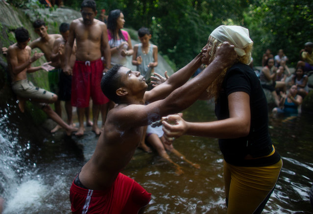 """In this photo taken October 12, 2019, a man's eyes roll backwards as he partakes in a ritual with a spiritual healer known as a """"madrina"""" on Sorte Mountain where followers of indigenous goddess Maria Lionza gather annually in Venezuela's Yaracuy state. Venezuela is predominantly Roman Catholic, and while the church disapproves of the folk religion, it has long since abandoned its attempts to suppress it. (Photo by Ariana Cubillos/AP Photo)"""