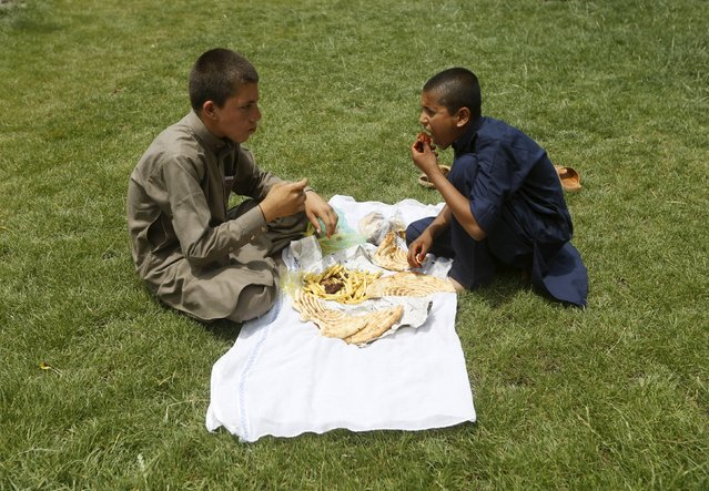 Afghan boys eat their lunch at a park, during the first day of the Muslim holiday of Eid-al-Fitr, marking the end of the holy month of Ramadan, in Kabul, Afghanistan, July 17, 2015. (Photo by Omar Sobhani/Reuters)