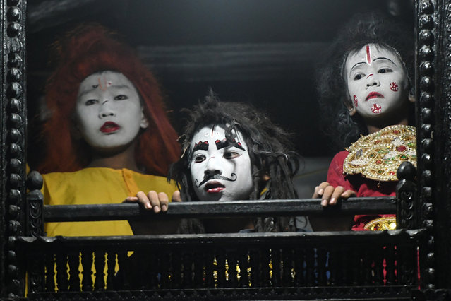 "Nepali young artists with painted face look out from a window before performing in a play based on Hindu mythology at Basantapur Durbar Square on the second to last day of the ""Indra Jatra"" Hindu festival in Kathmandu on September 16, 2019. (Photo by Prakash Mathema/AFP Photo)"